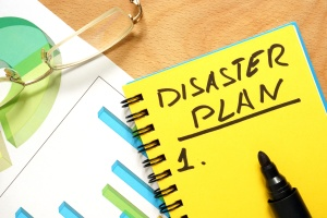 Notepad with disaster plan on a wooden table.